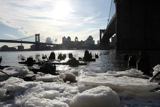 Ice forms under the Brooklyn Bridge, right, on the Manhattan side of the East River in New York on Monday, Feb. 16, 2015. Temperatures in the city were in the single digits on Monday morning. The Manhattan Bridge is at background left. (AP Photo/Peter Morgan) ORG XMIT: NYPM103 Photo: Peter Morgan / AP