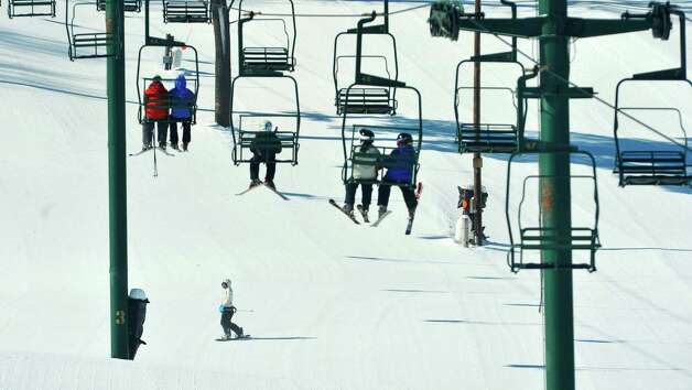 Skiers make their way up for another run as a snowboarder comes down at Maple Ski Ridge on Monday, Feb. 16, 2015, in Rotterdam, N.Y.  The ski hill offers a full day program from 8:30am to 3pm during the school break.  The ski hill is also holding the Snow Box Derby on February 21st.  (Paul Buckowski / Times Union) Photo: Paul Buckowski / 00030357A