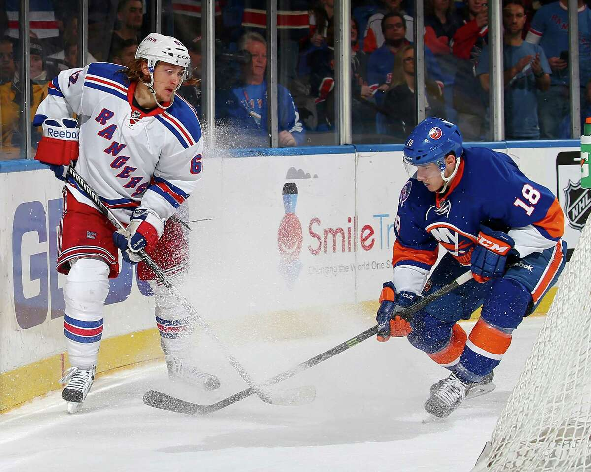 UNIONDALE, NY - FEBRUARY 16: Carl Hagelin #62 of the New York Rangers tries to keep the puck from Ryan Strome #18 of the New York Islanders in the third period on February 16, 2015 at the Nassau Veterans Memorial Coliseum in Uniondale,New York.The New York Rangers defeated the New York Islanders 6-5. (Photo by Elsa/Getty Images) ORG XMIT: 507049761