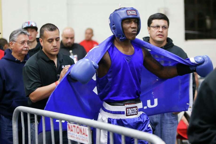 Kamryn Dyungy (right) fighting with the USAF, prepares to enter the ring followed by coaches Bobby De Leon and Osmar Alaniz during opening night of the 2015 San Antonio Regional Golden Gloves boxing tournament at Woodlawn Gym on Monday, Feb. 16, 2015.  MARVIN PFEIFFER/ mpfeiffer@express-news.net Photo: Marvin Pfeiffer /San Antonio Express-News / Express-News 2015