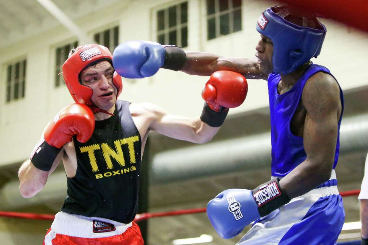 Kamryn Dungy (right) fighting with the USAF, trades punches with Bryan Vasquez, fighing unattached, during opening night of the 2015 San Antonio Regional Golden Gloves boxing tournament at Woodlawn Gym on Monday, Feb. 16, 2015. MARVIN PFEIFFER/ mpfeiffer@express-news.net
