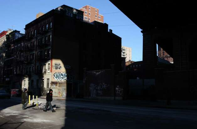 Two men walk through a patch of sunlight under the Manhattan Bridge in New York on Monday, Feb. 16, 2015. Temperatures were in the single digits in the city on Monday morning. (AP Photo/Peter Morgan) ORG XMIT: NYPM105 Photo: Peter Morgan / AP