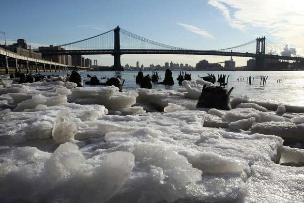 Ice forms along the shore of the Manhattan side of the East River in New York on Monday, Feb. 16, 2015. Temperatures in the city were in the single digits on Monday morning. The Manhattan Bridge is in the background. (AP Photo/Peter Morgan) ORG XMIT: NYPM101 Photo: Peter Morgan / AP