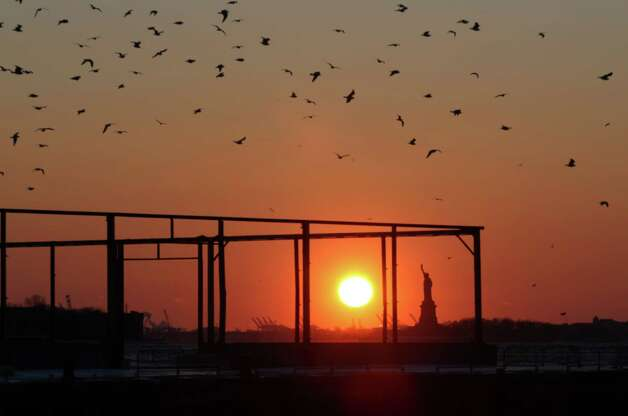 Seagulls fly over the Brooklyn waterfront as the sun sets behind the Statue of Liberty in New York on Sunday, Feb. 15, 2015. An extremely cold air mass is moving into the region on Sunday night. (AP Photo/Peter Morgan) ORG XMIT: NYPM104 Photo: Peter Morgan / AP