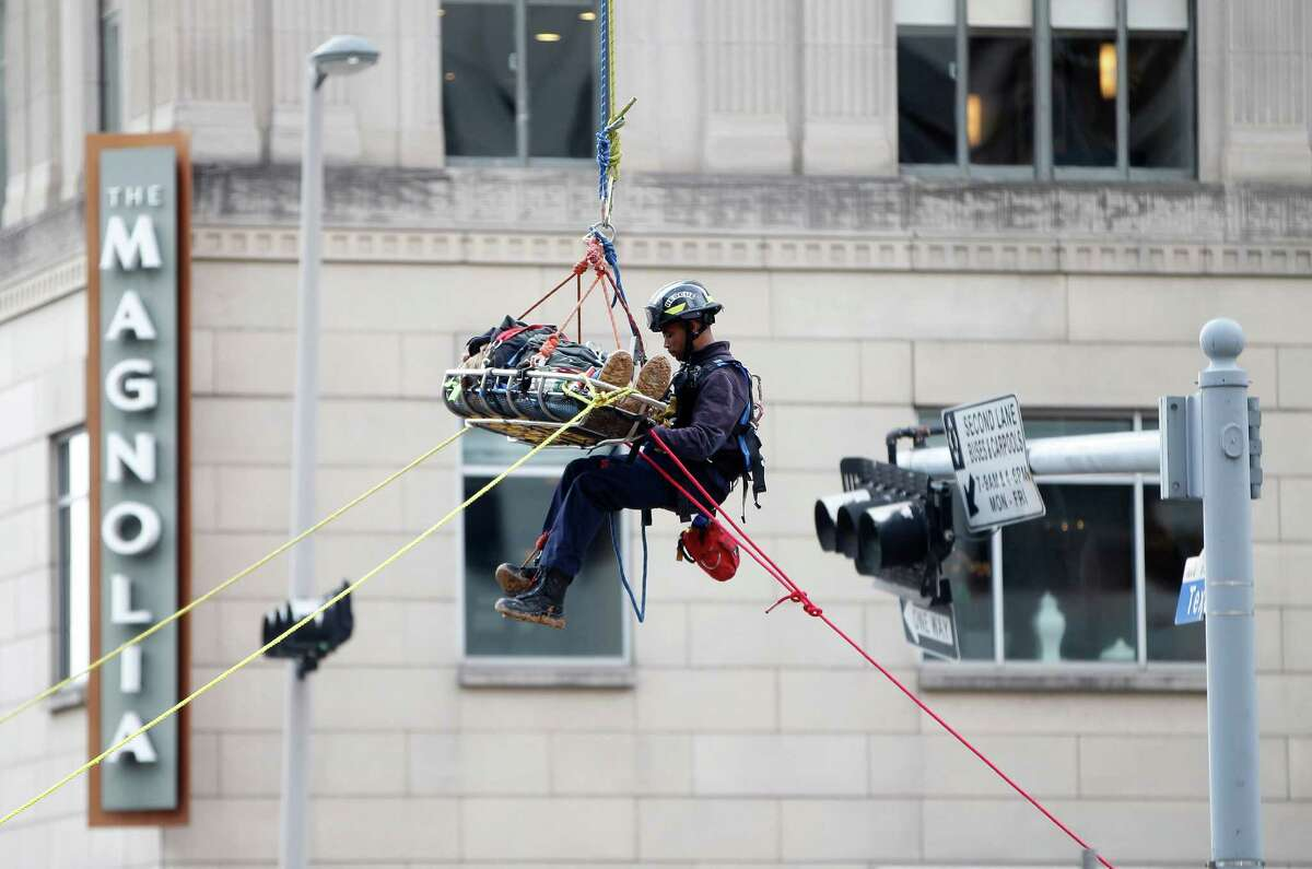 Houston firefighters rescue a worker, who fell from a platform at a construction site, Tuesday, Feb. 17, 2015, in downtown Houston. The man fell off a platform about 9 a.m., falling about 15-20 feet, Houston fire department officials said. The site is in the 1000 block of Texas, east of the Rice Hotel.The extent of the man's injuries is not known.