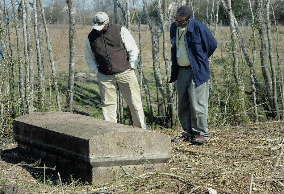 "Everette ""Bo"" Alfred, left, and Shedrick Evans look Friday at one of the graves discovered in the recently cleared Jefferson County pauper's cemetery. The cemetery was overgrown with brush and small trees and is being enlarged to provide more than 9,000 plots.  Photo taken Friday February, 13, 2015   Guiseppe Barranco/The Enterprise Photo: Guiseppe Barranco, Photo Editor"