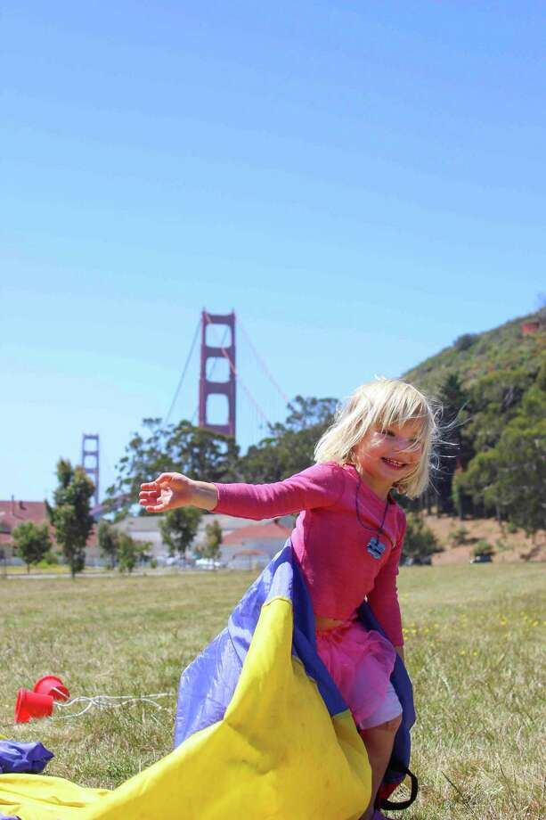 A camper plays with a parachute at the Big Discoveries camp, where preschoolers experience the freedom of the outdoors in San Francisco's local environment. Photo: Courtesy Of Bay Area Discovery M / ONLINE_CHECK