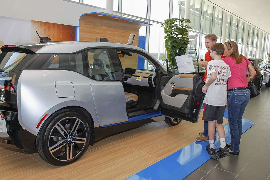 BMW of West Houston customers Ron and Catherine Gentry with their son, Ben, look at the new BMW i3 all-electric car. Photo: Diana L. Porter, Freelance / © Diana L. Porter