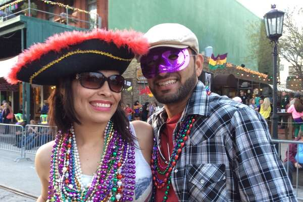 Revelers celebrate Mardi Gras in Galveston's historic Strand District on Saturday, February 14, 2015.