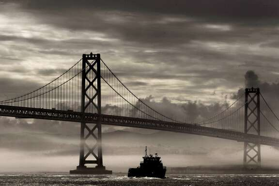 A break in the rain storms as fog and clouds fill the skies above the Bay Bridge, as seen from Treasure Island, on Thursday Dec. 9, 2010, in San Francisco, Calif.