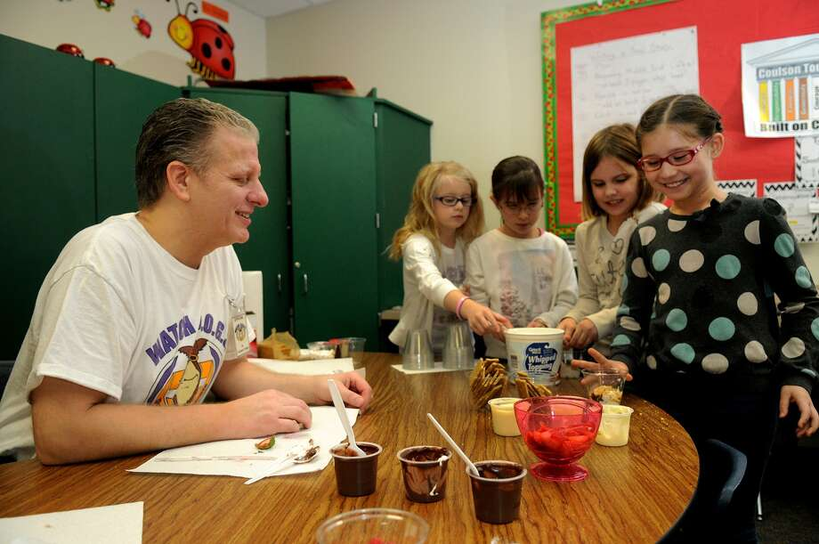 Volunteer Michael Bisbee, left, helps Ashley Pickering, Natalia Fuentes, Penelope Leto and Lizzy Ikenaga assemble parfaits at Tough Elementary. Photo: Jerry Baker, Freelance