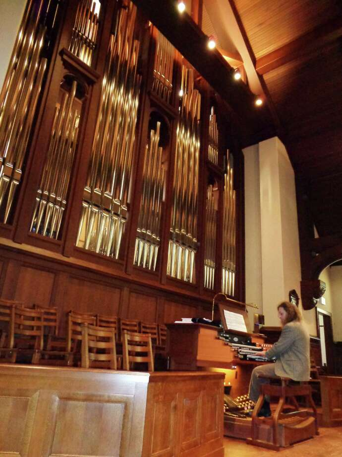 Aymeric Dupre la Tour, director of music  and organist at historic First Church Congregational, seems dwarfed by the pipes of the Klais organ in the church sanctuary during Organ Crawl on Monday. Photo: Meg Barone / Fairfield Citizen
