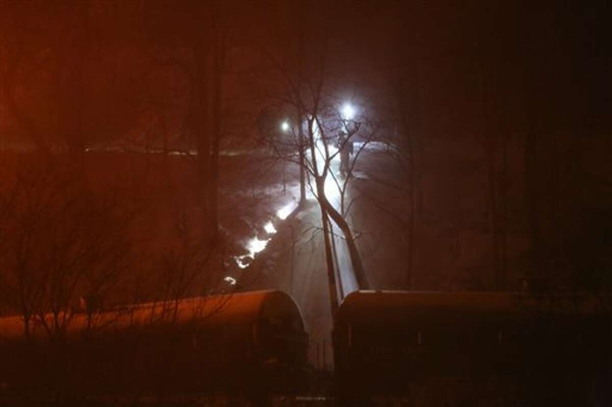 Firefighters inspect derailed train cars near Mount Carbon, W.Va., Monday, Feb. 16, 2015. A CSX train carrying more than 100 tankers of crude oil derailed in a snowstorm, sending a fireball into the sky and threatening the water supply of nearby residents, authorities and residents said Tuesday. (AP Photo/The Daily Mail, Marcus Constantino)