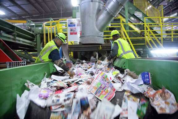Waste Management employees work quickly to remove nonrecyclable materials from a conveyor belt at the Waste Management Recycling Facility in southwest Houston. Nonrecyclables and material contaminated by food cost operators time and money.