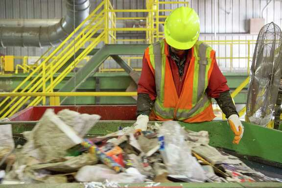 A Waste Management  employee works quickly to remove non recyclable materials from a conveyor belt filled with recyclable garbage Thursday November 20, 2014  at the Waste Management Recycling Facility in Southwest Houston, TX. (Billy Smith II / Houston Chronicle)