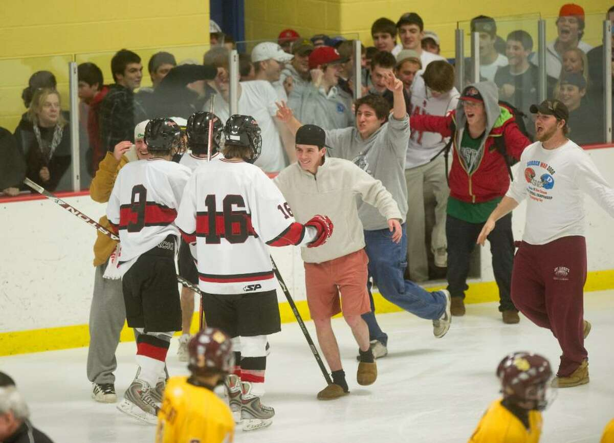 New Canaan celebrates after defeating St. Joes 4-3 in overtime during the semi-final round of the FCIAC boys hockey tournament at Terry Conners Rink in Stamford, Conn. on Wednesday, March 3, 2010.