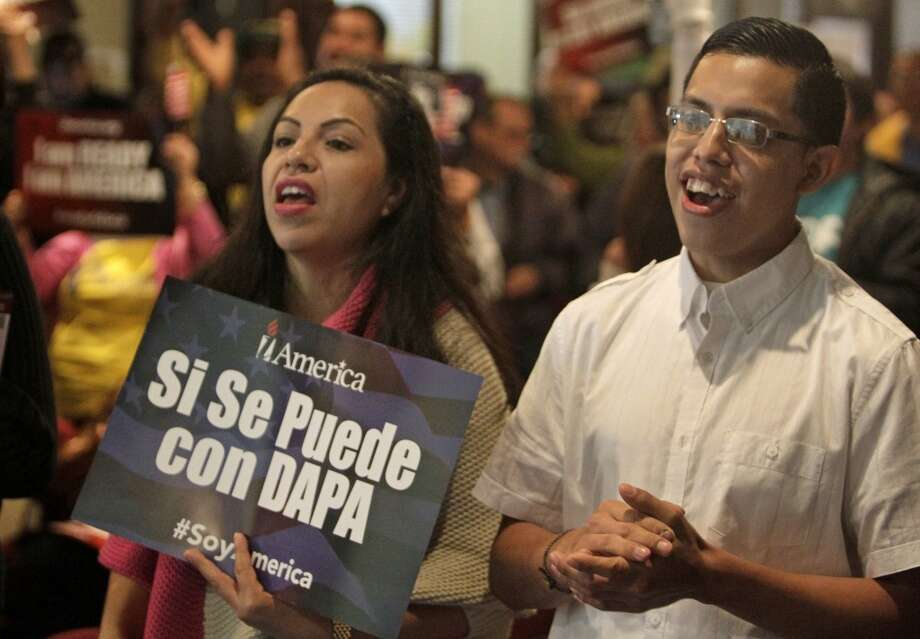 Alma Rodríguez, izq., y su hijo Steven Arteaga Rodríguez, der., aplauden durante un evento sobre las medidas de inmigración del presidente Barack Obama, pese a que fueron suspendidas temporalmente por un juez federal de Brownsville. Photo: Melissa Phillip, Houston Chronicle