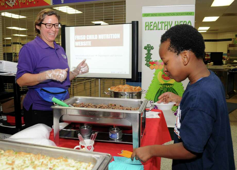 Maria Pedraza with Fort Bend Independent School District Food Service waits for a reaction from fourth-grader Buchi Okoro on the lettuce wrap served during the Fort Bend ISD's Child Nutrition Department 23rd annual Epicurean Afternoon.   Maria Pedraza with Fort Bend Independent School District Food Service waits for a reaction from fourth-grader Buchi Okoro on the lettuce wrap served during the Fort Bend ISD's Child Nutrition Department 23rd annual Epicurean Afternoon. / Freelance