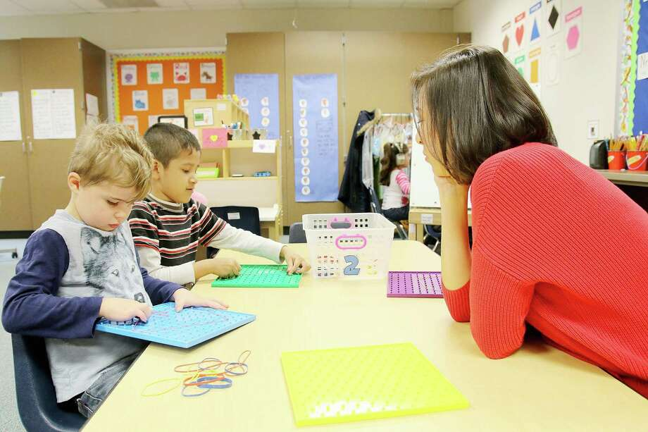 Teacher Ana Duplan instructs pupils Joshua Aaronson, left, and Joseph Olvera in her pre-kindergarten class at Greene Elementary School in the Clear Creek school district. Photo: Pin Lim, FreelANCE / Copyright Forest Photography, 2015.