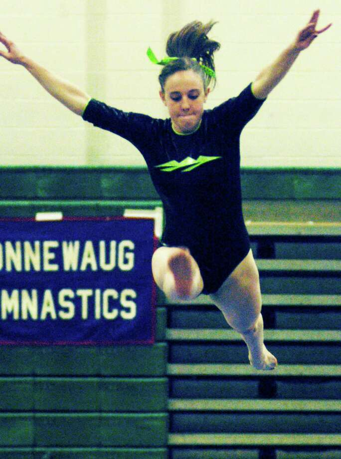 Erica Davidson of the Green Wave virtually takes flight as she performs her gold medal-winning routine on the balance beam for New Miford High School gymnastics during the South-West Conference championship meet, Feb. 12, 2015 at NMHS. Photo: Norm Cummings / The News-Times