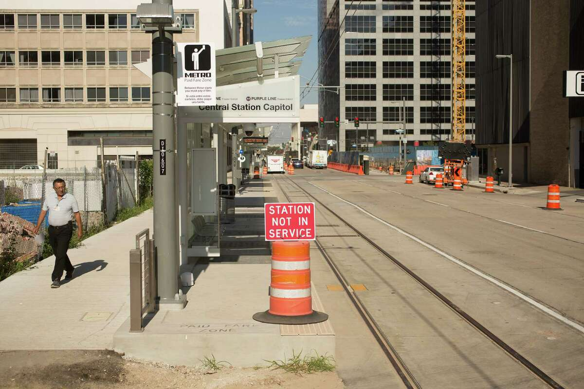 A pedestrian walks past the new Green/Purple MetroRail Line station on Capitol at Fannin downtown Wednesday, Oct. 22, 2014, in Houston.