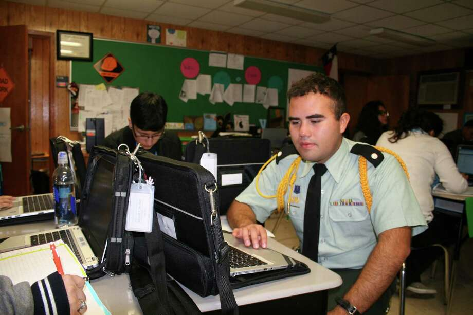 Ramsey Victor, a senior at High School for Law Enforcement and Criminal Justice, said the laptop he and other seniors at his school received through an HISD program is helping him learn the rules of punctuation. Photo: Tom Behrens