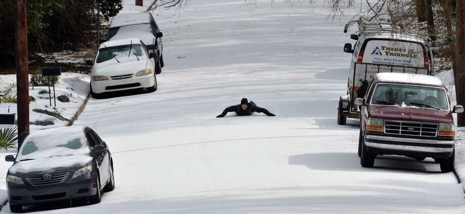 Oscar Barbaza enjoys an empty Sprunt Ave., Tuesday, Feb. 17, 2015, in Durham, N.C. A snow and ice storm blasted parts of the Mid-Atlantic and the South, creating treacherous road conditions and leaving hundreds of thousands without power.  Photo: Chuck Liddy, Associated Press / The News & Observer