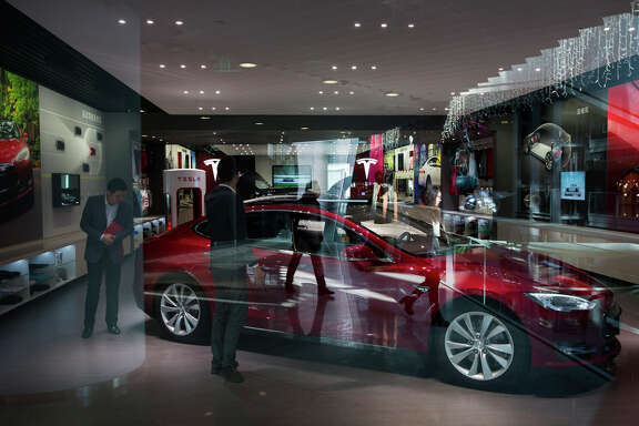 Customers browse at a Tesla showroom in Beijing last month. The Palo Alto carmaker, which is rapidly expanding, may be thinking more seriously about a collaboration with Apple.