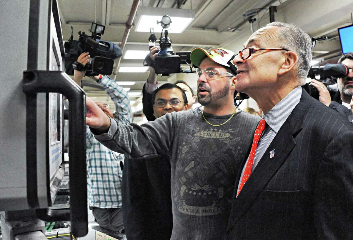 Machine operator Chris Dake, center, of Fort Edward demonstrates a paper sheeting machine operation to U.S. Senator Charles Schumer, right, during the senator's tour of Finch Paper Tuesday, Feb. 17, 2015, in Glens Falls, N.Y. (John Carl D'Annibale / Times Union)