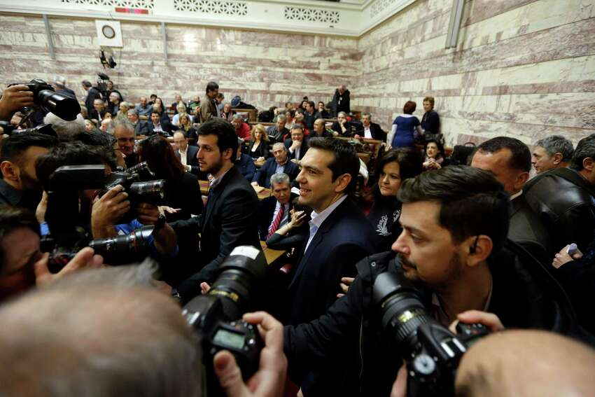 Greece's Prime Minister Alexis Tsipras, centre right, is surrounded by photographers and security as he arrives for a speech to his party's lawmakers at the parliament in Athens, on Tuesday, Feb. 17, 2015. Tsipras is facing increasing pressure from international lenders to seek an extension of the country's bailout. During his speech, he announced that his party would endorse former conservative interior minister Prokopis Pavlopoulos as candidate for the country's new president. (AP Photo/Thanassis Stavrakis) ORG XMIT: ATH111