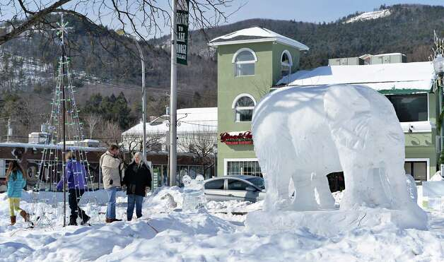 Visitors pass a large elephant snow sculpture by Tony DeStratis and Jerry Merrill during the First Annual Lake George Snow Sculpture Contest in Shepard Park Tuesday Feb. 17, 2015 in Lake George, NY.  (John Carl D'Annibale / Times Union) Photo: John Carl D'Annibale / 00030637A
