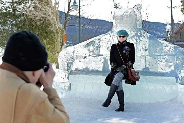 Tracey Herrington of Dansville, NY, poses on an ice sculpture for her husband Mark Sager, left, during the First Annual Lake George Snow Sculpture Contest in Shepard Park Tuesday Feb. 17, 2015 in Lake George, NY.  (John Carl D'Annibale / Times Union) Photo: John Carl D'Annibale / 00030637A