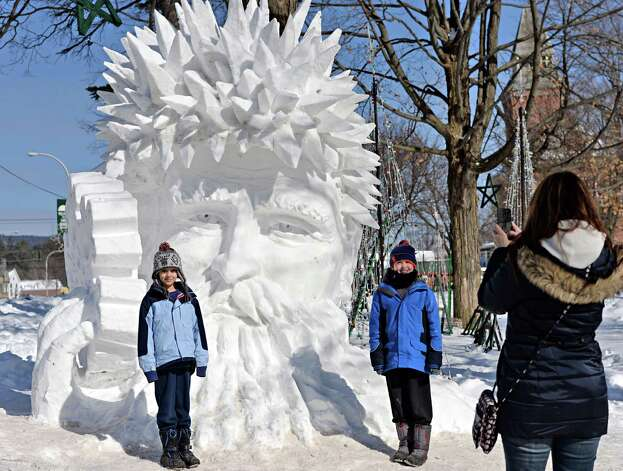 Deb Young, right, of Tully, NY, takes a photo of her children Willard,left, 9, and Tanner, 11, beside a snow sculpture by Peter Vogelaar and Glenn Durlacher during the First Annual Lake George Snow Sculpture Contest in Shepard Park Tuesday Feb. 17, 2015 in Lake George, NY.  (John Carl D'Annibale / Times Union) Photo: John Carl D'Annibale / 00030637A