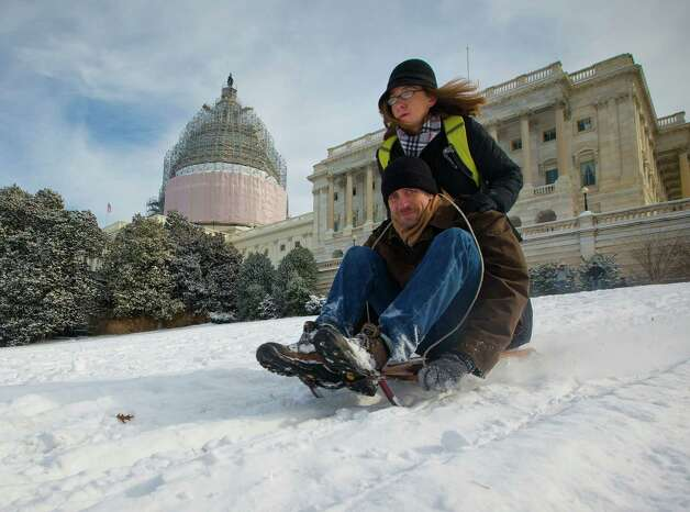 Amanda Batla and her husband Aaron Batla sled together on the slopped hill on Capitol Hill in Washington, Tuesday, Feb. 17, 2015, after a winter storm in the Washington area. The season's first major snow storm to blast large parts of the South and dropped up to 8 inches of snow around the Washington area. (AP Photo/Pablo Martinez Monsivais) ORG XMIT: DCPM107 Photo: Pablo Martinez Monsivais / AP