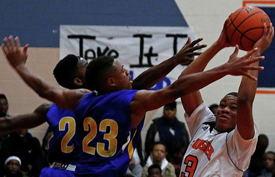 Elkins' Bryce Terrell left, and Nathaniel Cephas center, double team Bush's  Brendon Ganaway right, during third quarter boys high school basketball game action at Bush High School Tuesday, Feb. 17, 2015, in Richmond. Photo: James Nielsen, Houston Chronicle / © 2015  Houston Chronicle