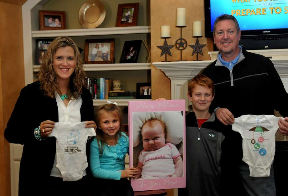 """Jaime Connell, left, and husband Randy, with daughter Hope, 4, and son Chase, 8, show off the """"onesie"""" they designed with instructions on how a baby should be placed when sleeping to prevent sudden infant death syndrome. The Connells are Realtors who lost their baby Jordan, in photo, to SIDS and started the My Baby Jordan Foundation to help others. Photo: Jerry Baker, Freelance"""