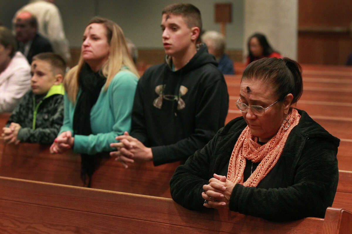 Faithful kneel by pews after receiving ashes on Ash Wednesday February 18, 2015 at Saint Mark the Evangelist Church in San Antonio.