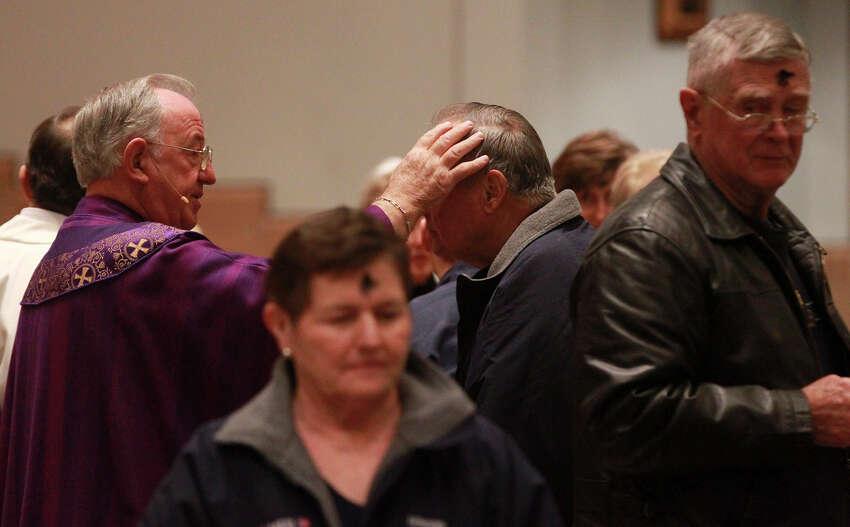Faithful receive ashes from Monsignor Michael O'Gorman (left) on Ash Wednesday February 18, 2015 at Saint Mark the Evangelist Church in San Antonio.