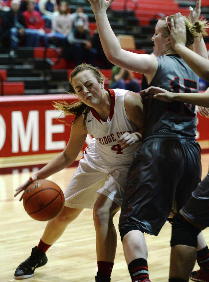 Bridge City's Shayla Bratton, No. 4, collides with Huffman Hargrave's Karlee White, No. 15, as she maneuvers for a shot Tuesday. The Bridge City Lady Cardinals took on the Huffman Hargrave Lady Falcons at Kountze High School on Tuesday night. Photo taken Tuesday 2/17/15 Jake Daniels/The Enterprise Photo: Jake Daniels / ©2014 The Beaumont Enterprise/Jake Daniels