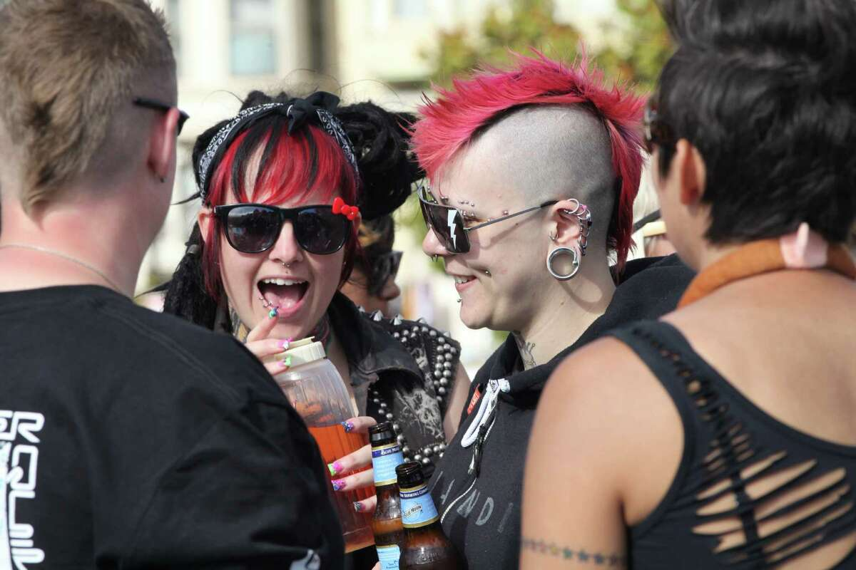 """Studded out, Nico Norris, left, and Toni Kotar, both from Oakland chat with friends in Dolores Park where the Dyke March themed """"better Together"""" will start on """"Pink"""" Saturday in San Francisco, Calif. on Saturday, June 25, 2011. Kat Wade / Special to the Chronicle"""