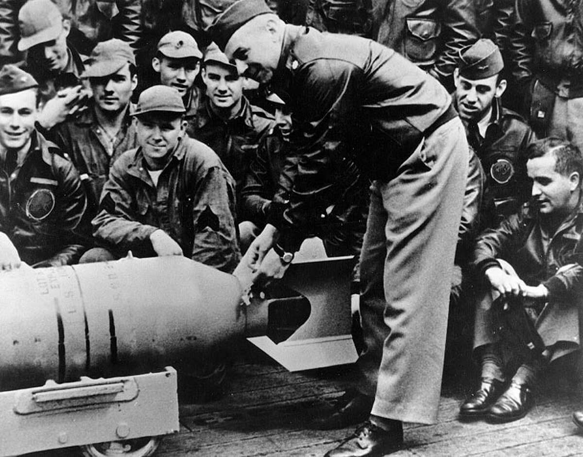 Lt. Col. Jimmy Doolittle, leader of the raiding force, wires a Japanese medal to a 500-pound bomb during ceremonies on the flight deck of the USS Hornet shortly before taking off for Japan in 1942.