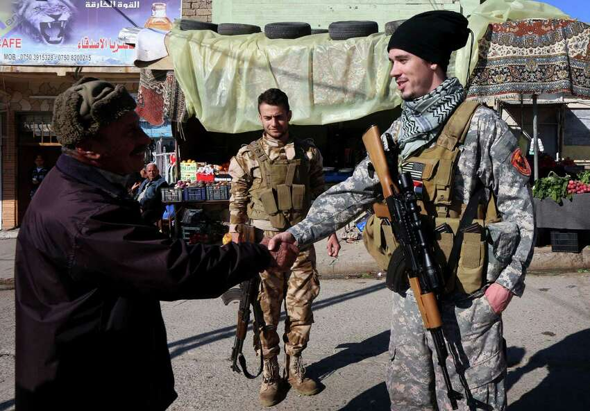 Brett (R), a 28-year-old US national who fights jihadists of the Islamic State (IS) group alongside Dwekh Nawsha, a Christian militia whose name is an Assyrian-language phrase conveying self-sacrifice, shakes hands of a passer-by on February 5, 2015, in the northern Iraqi town of Al-Qosh, located 35 km north of Mosul. The foreign contingent fighting IS is tiny compared to the thousands of foreigners who have joined the jihadist group, but interest is growing and 20 more volunteers already lined up to join. AFP PHOTO / SAFIN HAMED