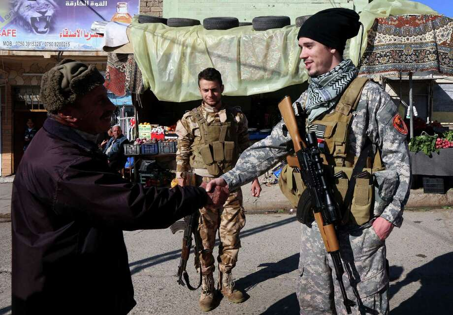 Brett (R), a 28-year-old US national who fights jihadists of the Islamic State (IS) group alongside Dwekh Nawsha, a Christian militia whose name is an Assyrian-language phrase conveying self-sacrifice, shakes hands of a passer-by on February 5, 2015, in the northern Iraqi town of Al-Qosh, located 35 km north of Mosul. The foreign contingent fighting IS is tiny compared to the thousands of foreigners who have joined the jihadist group, but interest is growing and 20 more volunteers already lined up to join. AFP PHOTO / SAFIN HAMED Photo: SAFIN HAMED, Getty Images / AFP