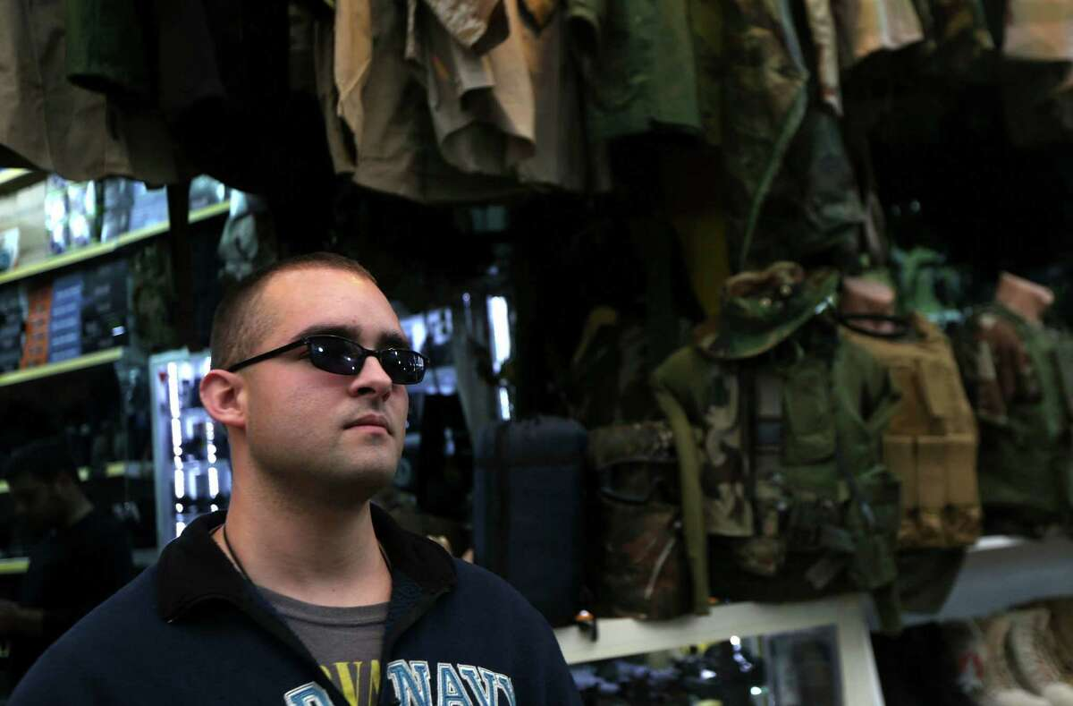 Louis Park, a US national who fights jihadists of the Islamic State (IS) group alongside Dwekh Nawsha, a Christian militia whose name is an Assyrian-language phrase conveying self-sacrifice, shops for military equipment at a market in the Iraqi city of Dohuk on February 5, 2015, before joining his contingent in the northern town of Al-Qosh, located 35 km north of Mosul. The foreign contingent fighting IS is tiny compared to the thousands of foreigners who have joined the jihadist group, but interest is growing and 20 more volunteers already lined up to join. AFP PHOTO / SAFIN HAMED