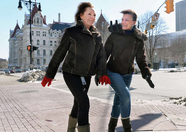 Maribeth Orciuoli, left, and Karen Ratigan, both of Wynantskill, keep warm by walking quickly and talking about Florida as they make their way back to work up Washington Avenue after lunch Friday Feb. 13, 2015, in Albany, NY.  (John Carl D'Annibale / Times Union) Photo: John Carl D'Annibale, Albany Times Union / 00030608A