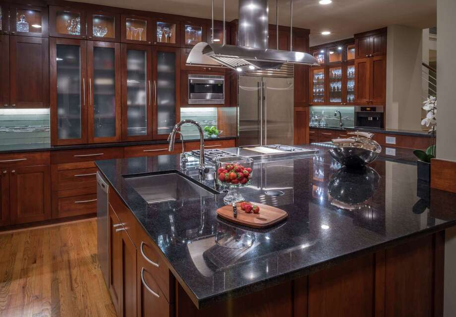 Even though she has plenty of countertop workspace, Jean Gould finds that she spends most of her kitchen time at the corner of the island closest to the sink. Along the walls, lighted cabinets showcase the glassware inside. Photo: Chuck Williams / Chuck Williams