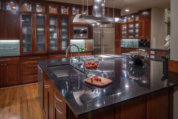 Even though she has plenty of countertop workspace, Jean Gould finds that she spends most of her kitchen time at the corner of the island closest to the sink. Along the walls, lighted cabinets showcase the glassware inside.