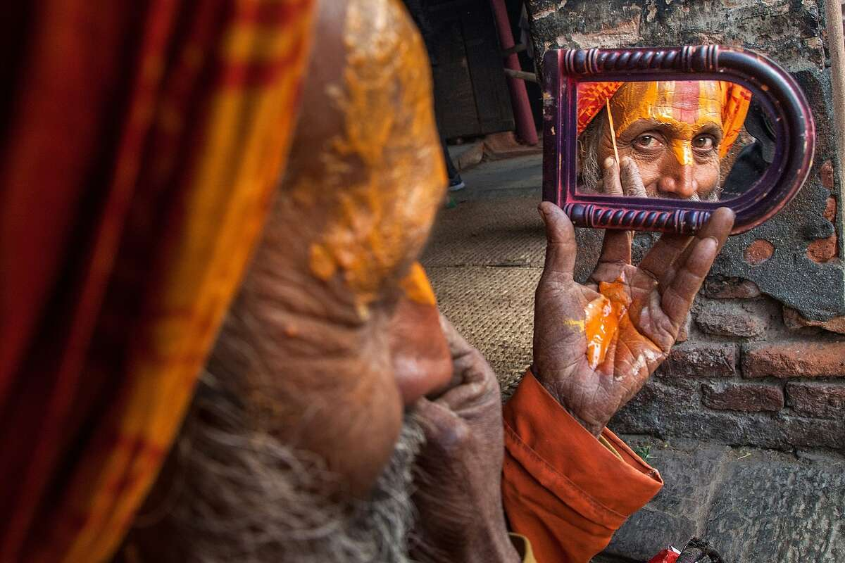 NO SUCH THING AS TOO MUCH MAKEUP: A sadhu, or Hindu holy man, applies paint to his face inside Pashupatinath temple during the celebration of the Maha Shivaratri festival in Kathmandu, Nepal. Close to 1 million devotees from different countries attend the festival, devoted to the god Shiva.