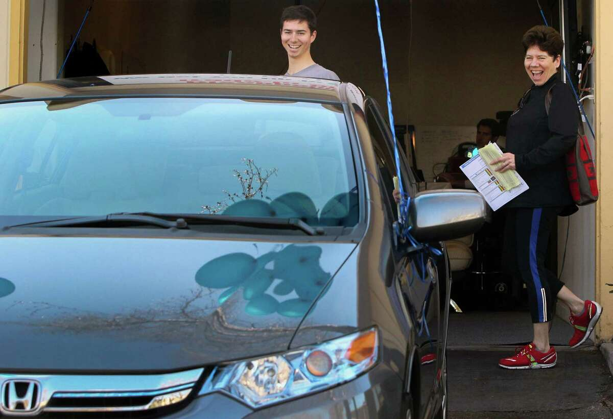Miles Bennett-Smith, left, and his mother Elena Bennett are all smiles after purchasing a 2013 Honda Insight from Carlypso, a new online service for used-car buyers, Saturday, Feb. 14, 2015, in San Carlos, Calif.