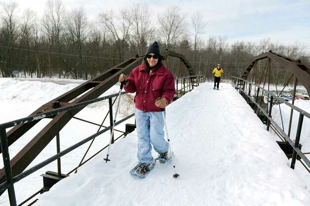 Carol Davis of Clifton Park, left, and her husband Bill Blain snowshoe across the Whipple Iron Truss Bridge on Wednesday, Feb. 18, 2015, at Vischer Ferry Nature and Historic Preserve in Clifton Park, N.Y. Clifton Park, with the Mohawk Towpath Byway, received $3,900 from Erie Canalway National Heritage Corridor to design and develop two trail entrance signs that identify the Vischer Ferry Nature & Historic Preserve?s entry points.(Cindy Schultz / Times Union) Photo: Cindy Schultz / 00030544A